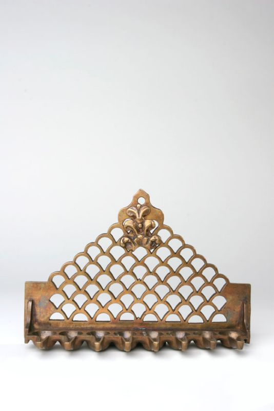 Hanukkah lamp adorned with wall structure and fleur-de-lis