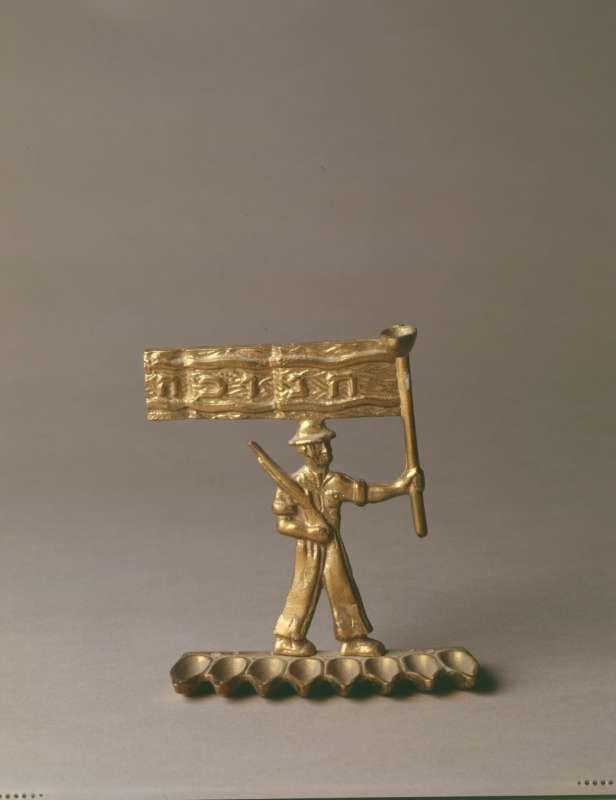 Hanukkah lamp with armed figure raising a flag
