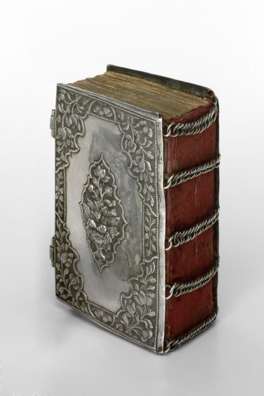 Bible book binding with five shaped chains on the spine, over red velvet
