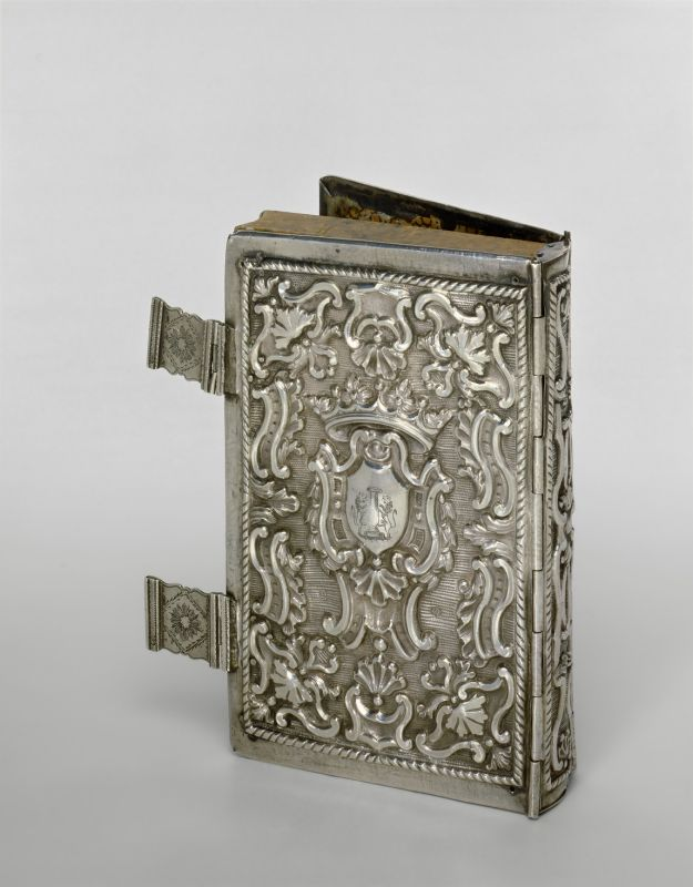 Book container in silver bookbinding form, adorned with family emblem