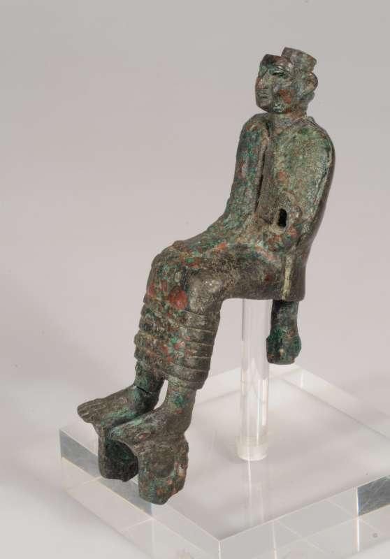 Figurine of a seated god(?) wearing a kilt, mantle, and, originally,  a headdress
