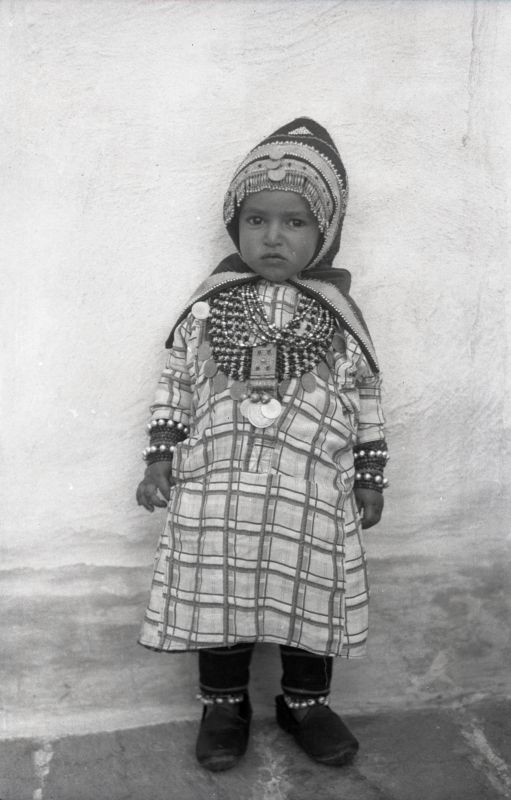 Small Jewish girl with elaborate headgear and amuletic jewelry