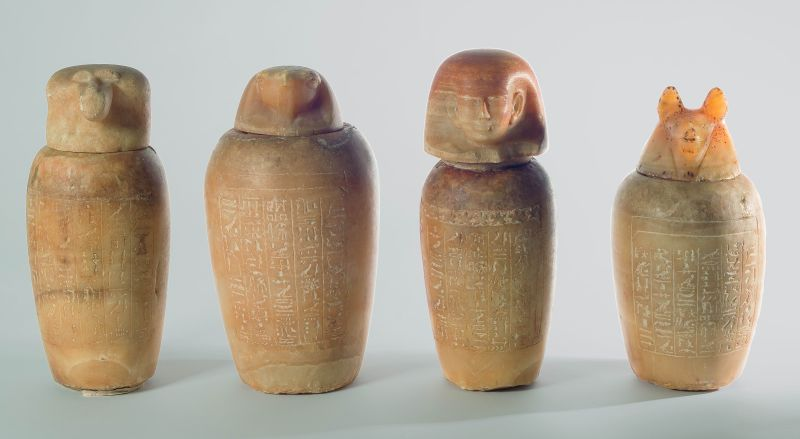 """Set of canopic jars of """"Ahmose, son of Psamtik, Scribe of the Treasury,"""" with stoppers depicting the four sons of Horus (guardians of the embalmed organs) and magical spells invoking their protection"""