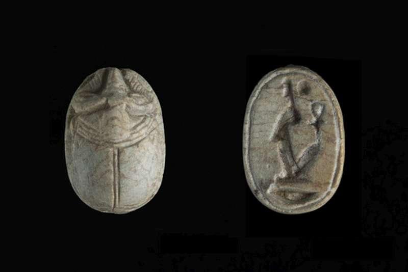 חרפושית שעל גבה מגולף ראש איל, ועל בסיסה דמות האלה מאעת מעל סימן