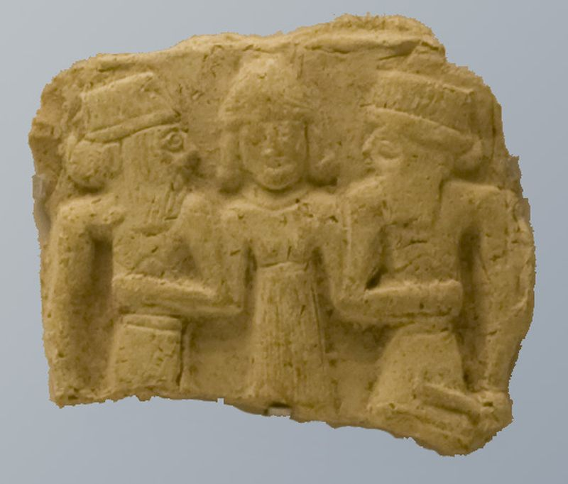Plaque depicting a goddess flanked by two gods