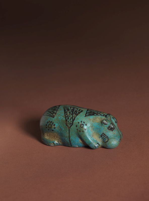 Figurine of a recumbent hippopotamus decorated with painted lotus flowers and probably symbolizing rebirth