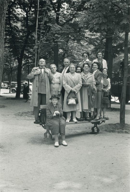 Group of People Standing on a Park Bench
