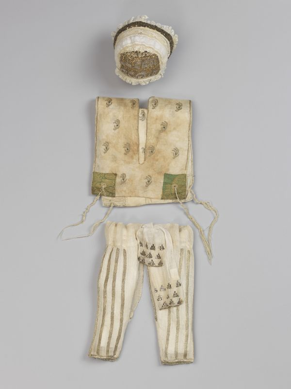 Outfit with miniature prayer shawl (<i>tallit</i>) for baby's circumcision, as an added sign of Jewish identity