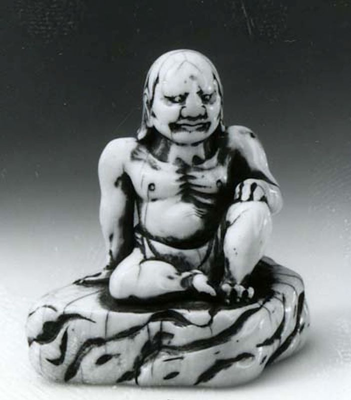 A disciple of Buddha sitting on a rock