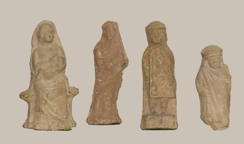 Cultic figurines: a woman holding an infant, a woman playing a lyre, a youth, and a chubby child