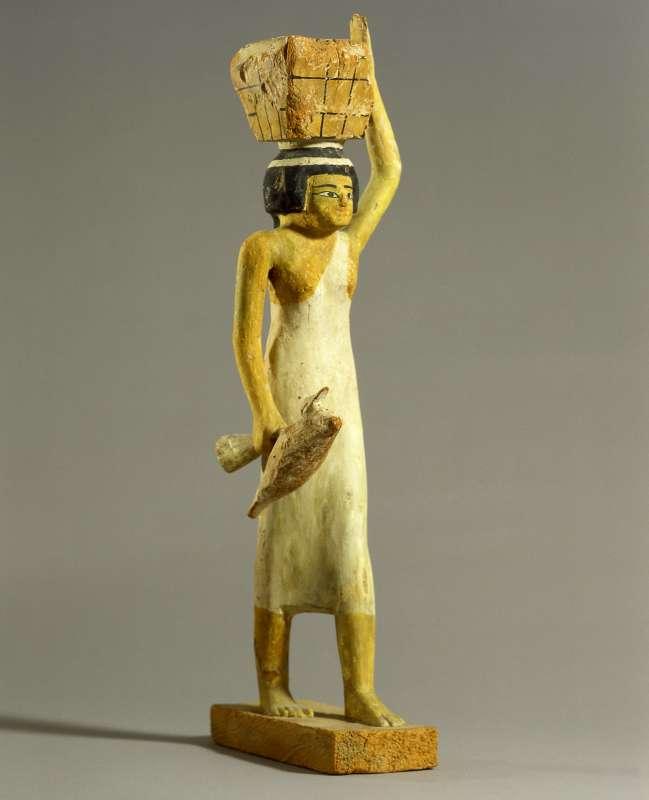 צלמית של נושאת מנחה שעל ראשה קופסת קמח ובידה ברווז